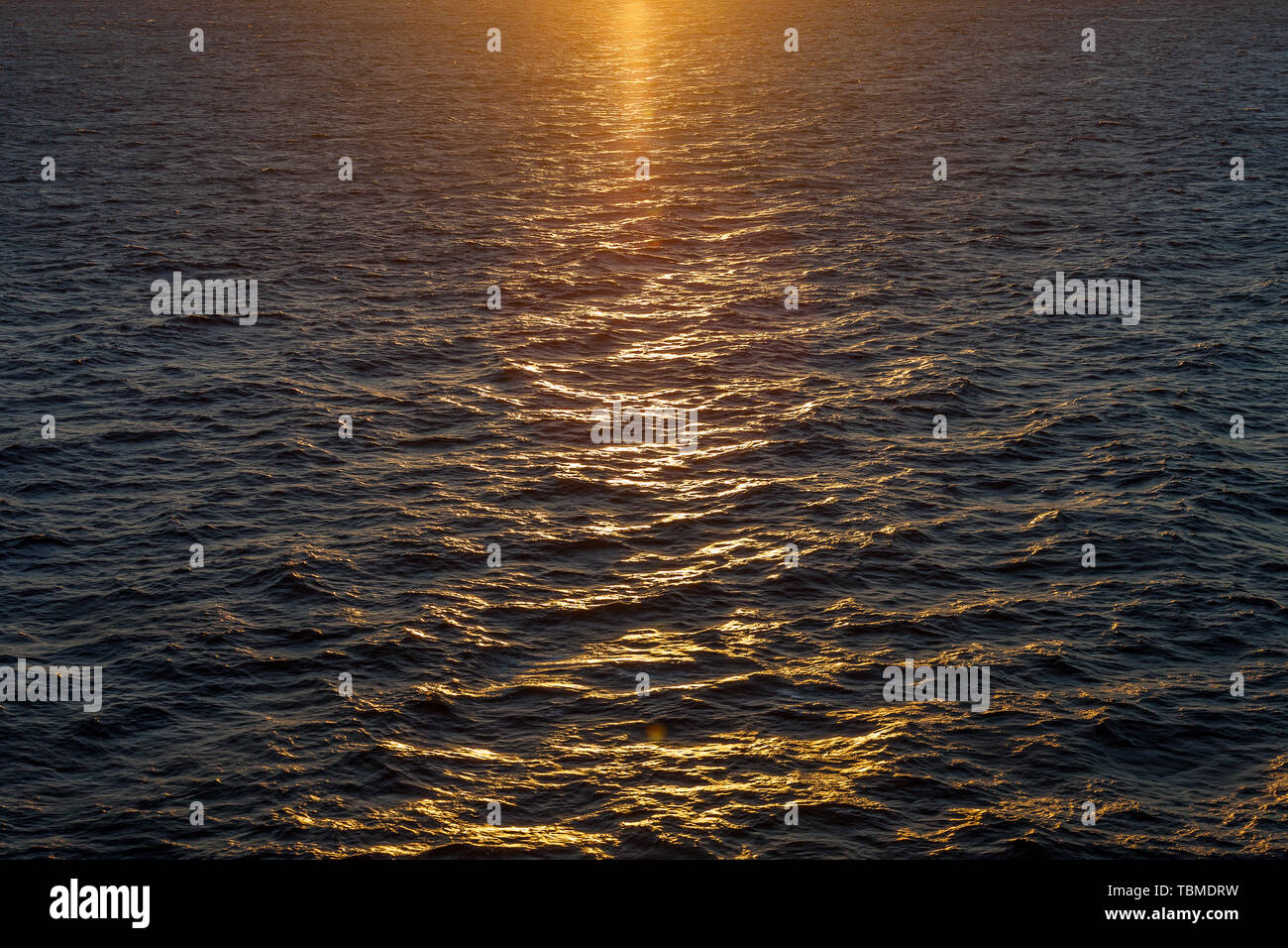 Beautiful reflections on the waves of the Mediterranean sea at sunset - Stock Image