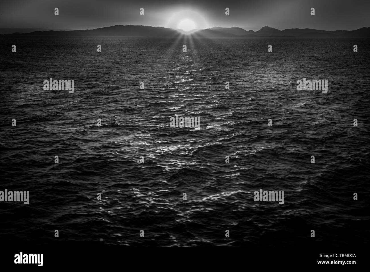 Black and white effect of sun about to set behind the Saronic Gulf islands Stock Photo