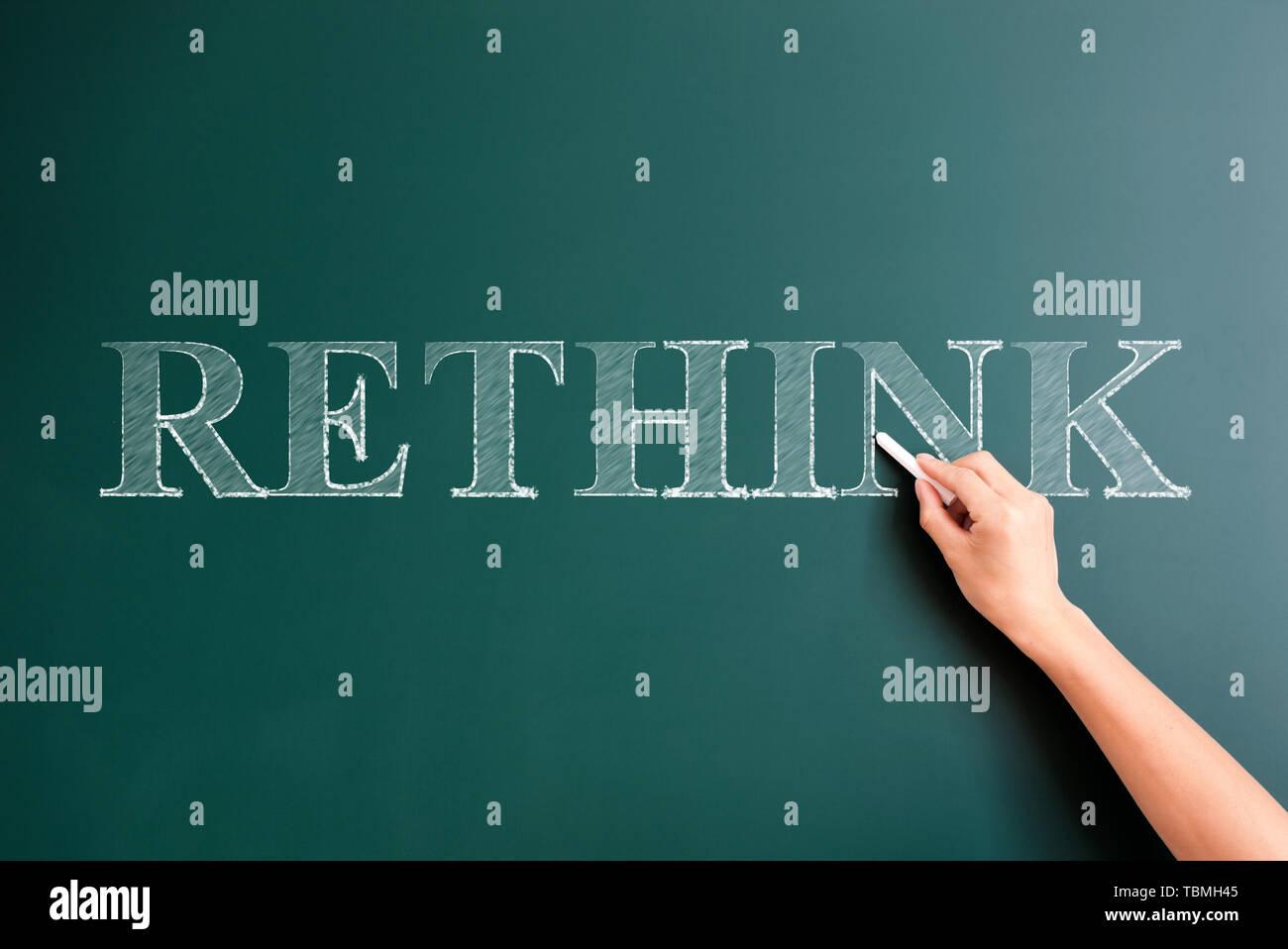 rethink written on blackboard - Stock Image