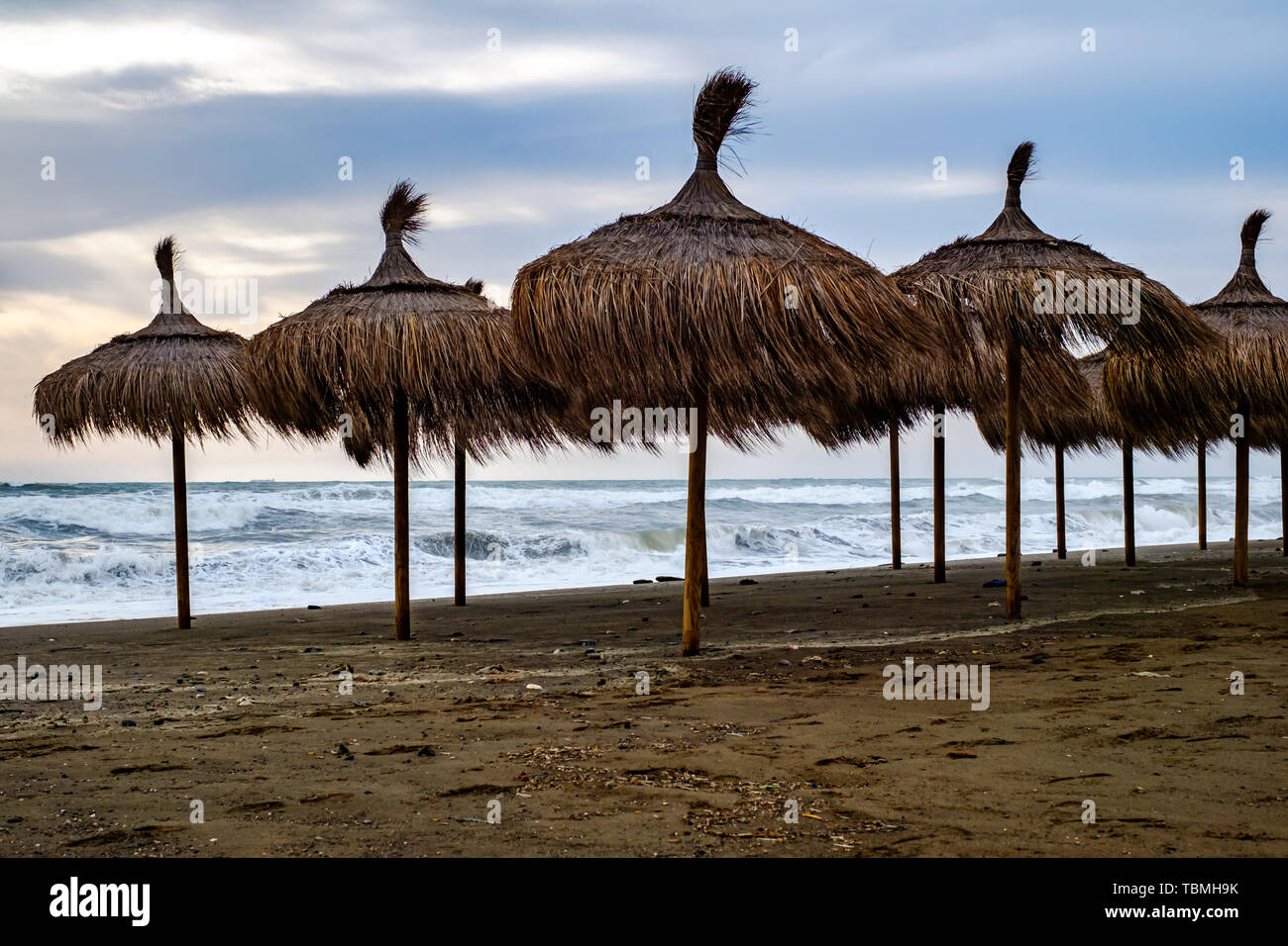 Straw umbrellas on the dirty beach on stormy day - Stock Image