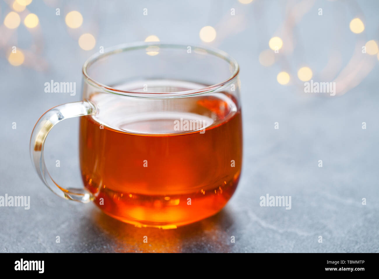 Tea in glass cup with light garland. Grey background. Copy space Stock Photo