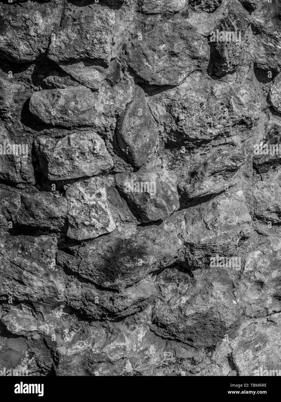 Background. Texture. The wall of multi-coloured stones agglomerated with cement mortar - Stock Image