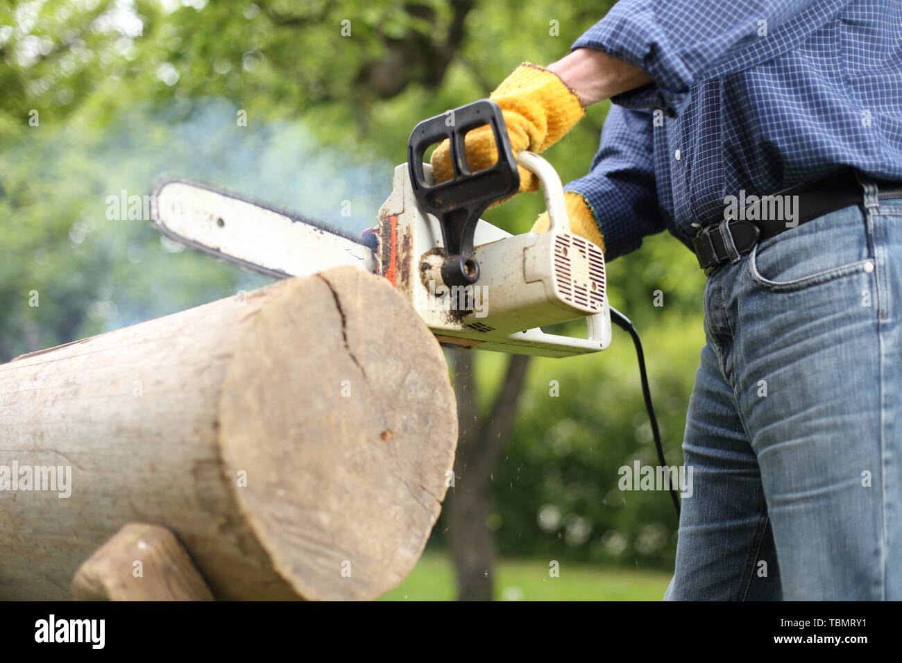Man working with a Dulled old chain of a Chainsaw Stock Photo