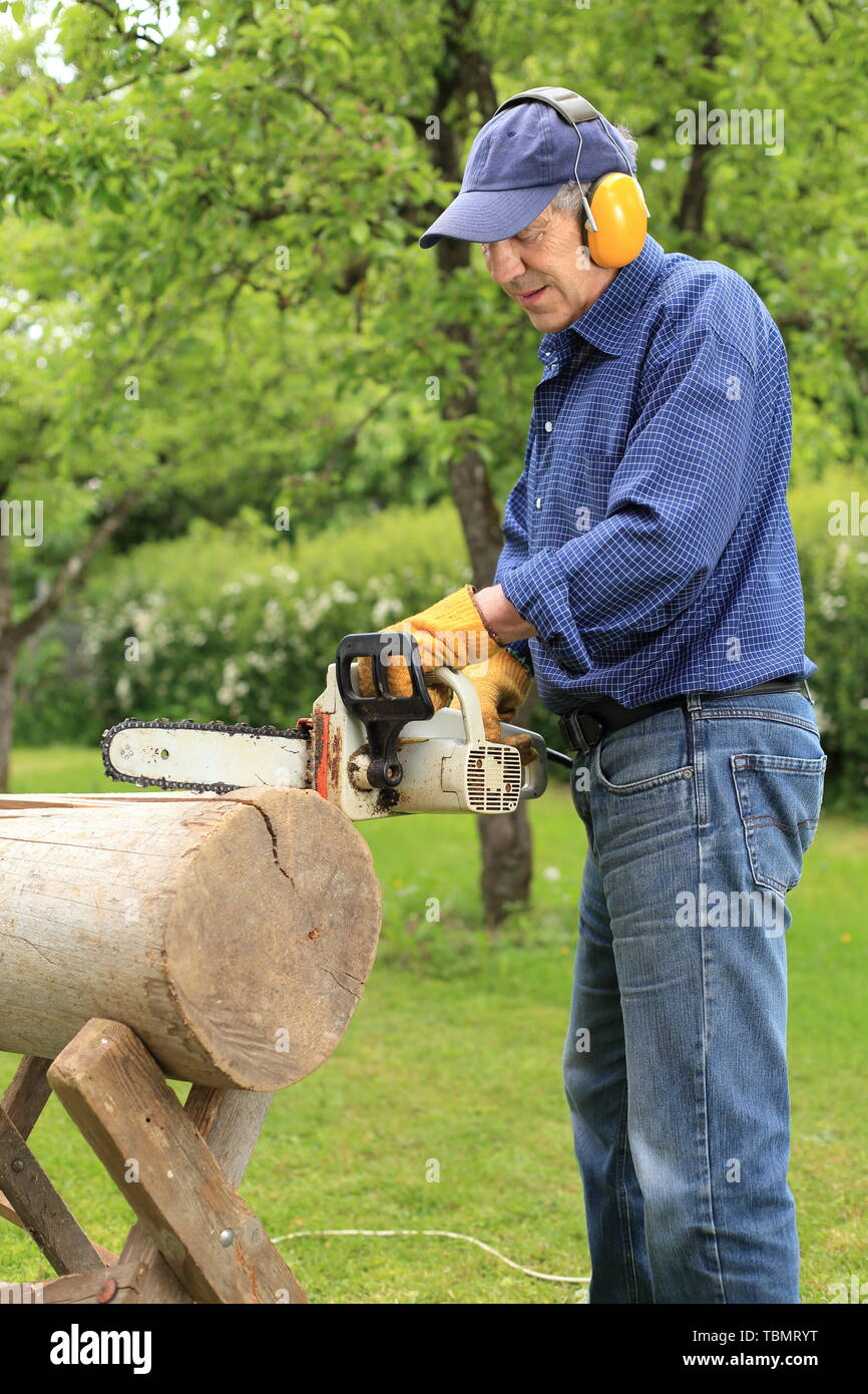 A Man working with a electric driven Chainsaw - Stock Image