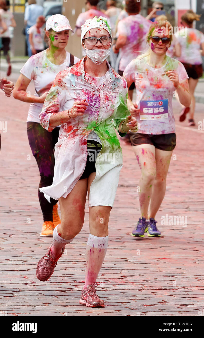 Woman with a nose mask, showered with colours runs during the event. The Color Run, also known as 'the happiest 5,000 meters on the planet', is an event series and paint race, its first event was in the United States in January 2012 since then the run has spread across the globe leaving a trail of color and happy runners across different continents and countries. The untimed event has no winners or prizes, but runners are showered with colored powder, made of food-grade corn starch, at stations along the run. In Ukrainian capital the first time Kyiv Color Run started in 2014. - Stock Image