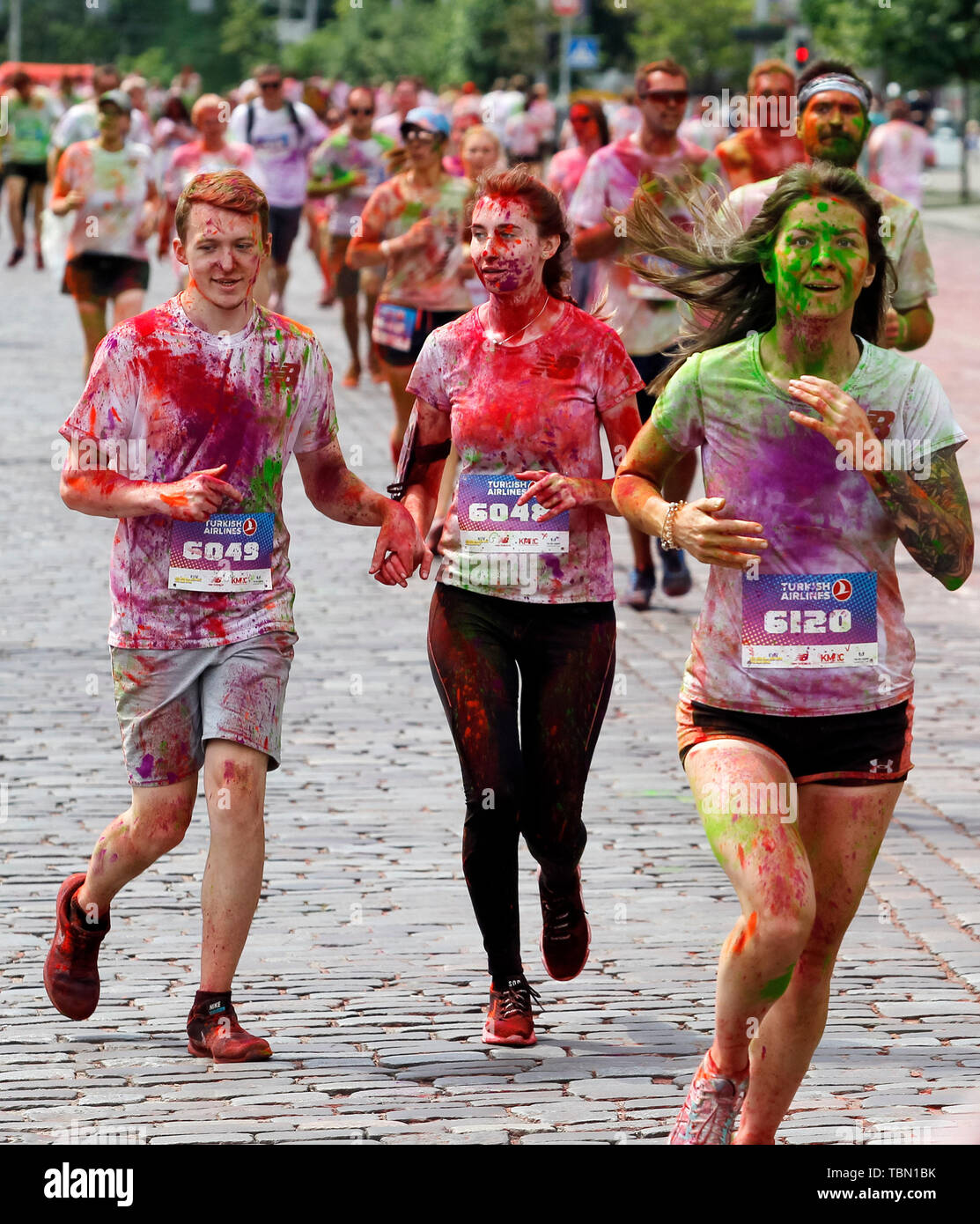 Participants run while showered with colours during the event. The Color Run, also known as 'the happiest 5,000 meters on the planet', is an event series and paint race, its first event was in the United States in January 2012 since then the run has spread across the globe leaving a trail of color and happy runners across different continents and countries. The untimed event has no winners or prizes, but runners are showered with colored powder, made of food-grade corn starch, at stations along the run. In Ukrainian capital the first time Kyiv Color Run started in 2014. - Stock Image