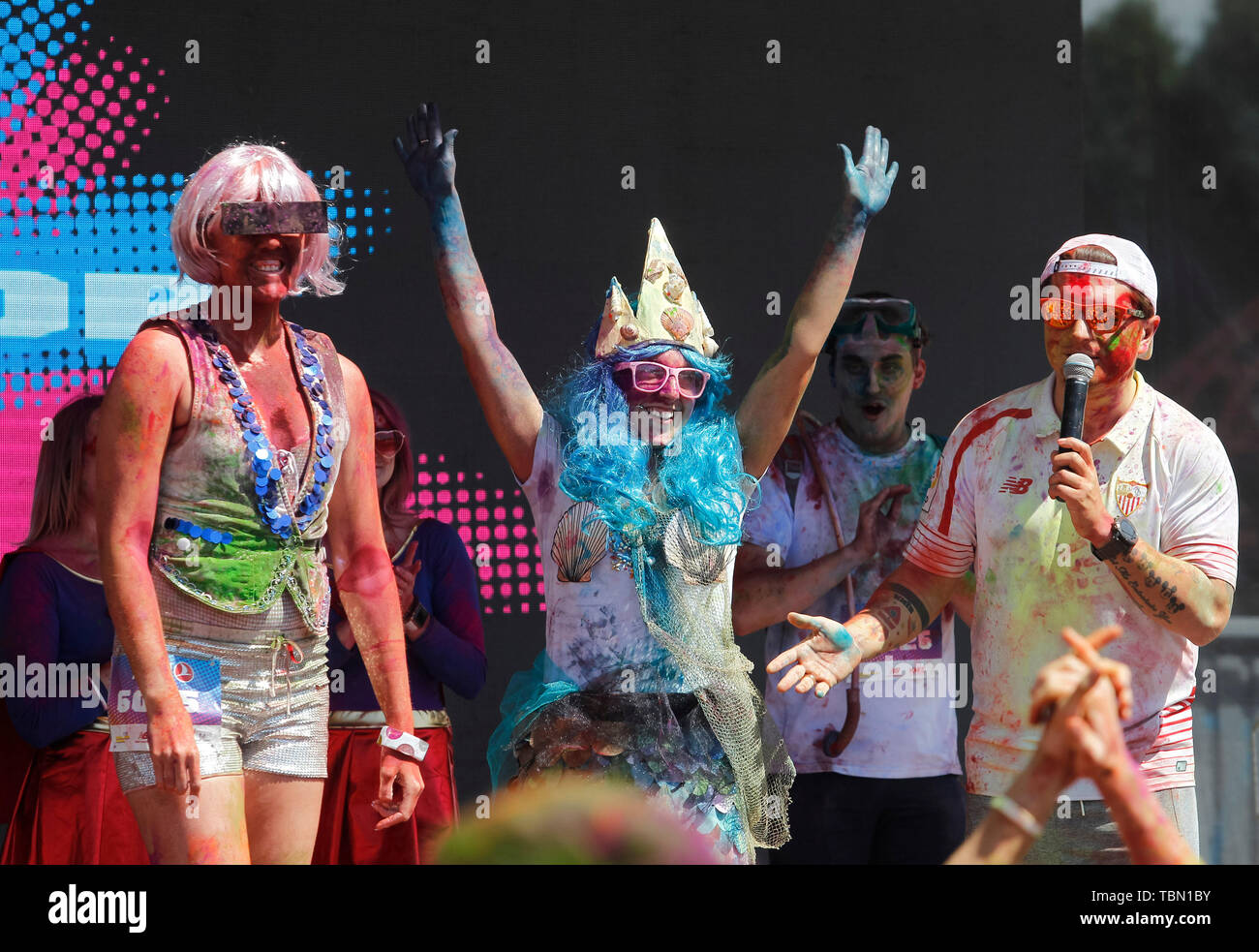 Participants on stage showered with colours during the event. The Color Run, also known as 'the happiest 5,000 meters on the planet', is an event series and paint race, its first event was in the United States in January 2012 since then the run has spread across the globe leaving a trail of color and happy runners across different continents and countries. The untimed event has no winners or prizes, but runners are showered with colored powder, made of food-grade corn starch, at stations along the run. In Ukrainian capital the first time Kyiv Color Run started in 2014. - Stock Image