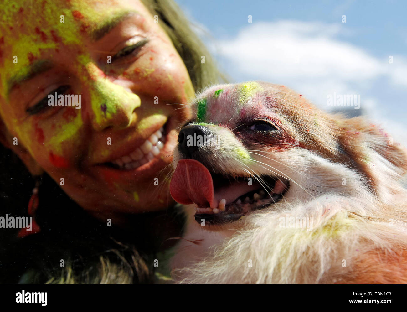 woman and her dog showered in colours during the run. The Color Run, also known as 'the happiest 5,000 meters on the planet', is an event series and paint race, its first event was in the United States in January 2012 since then the run has spread across the globe leaving a trail of color and happy runners across different continents and countries. The untimed event has no winners or prizes, but runners are showered with colored powder, made of food-grade corn starch, at stations along the run. In Ukrainian capital the first time Kyiv Color Run started in 2014. - Stock Image