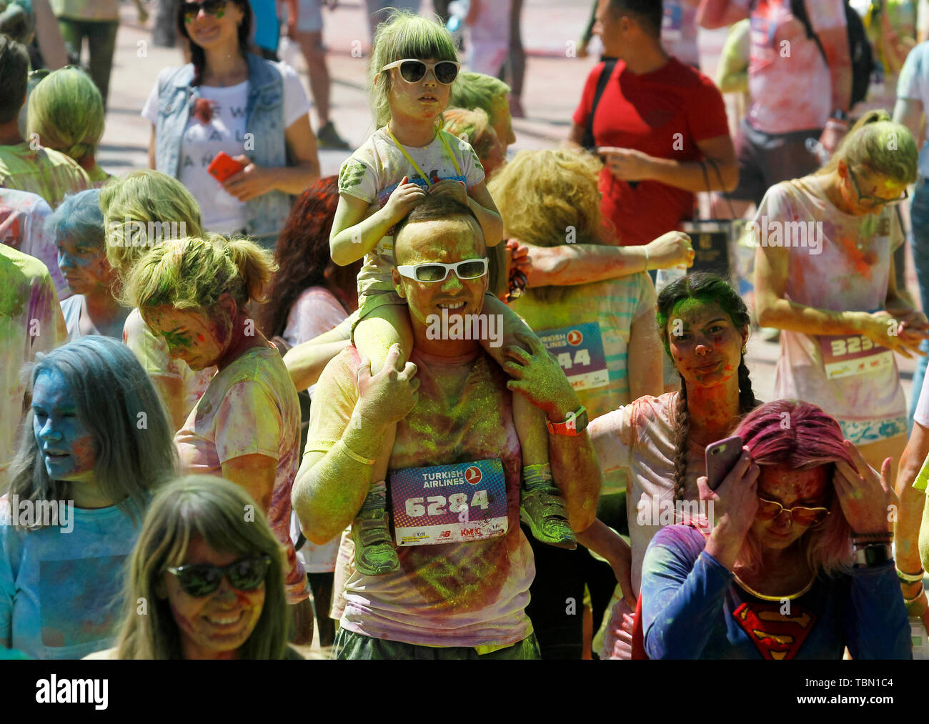 Man and daughter showered with colours during the event. The Color Run, also known as 'the happiest 5,000 meters on the planet', is an event series and paint race, its first event was in the United States in January 2012 since then the run has spread across the globe leaving a trail of color and happy runners across different continents and countries. The untimed event has no winners or prizes, but runners are showered with colored powder, made of food-grade corn starch, at stations along the run. In Ukrainian capital the first time Kyiv Color Run started in 2014. - Stock Image