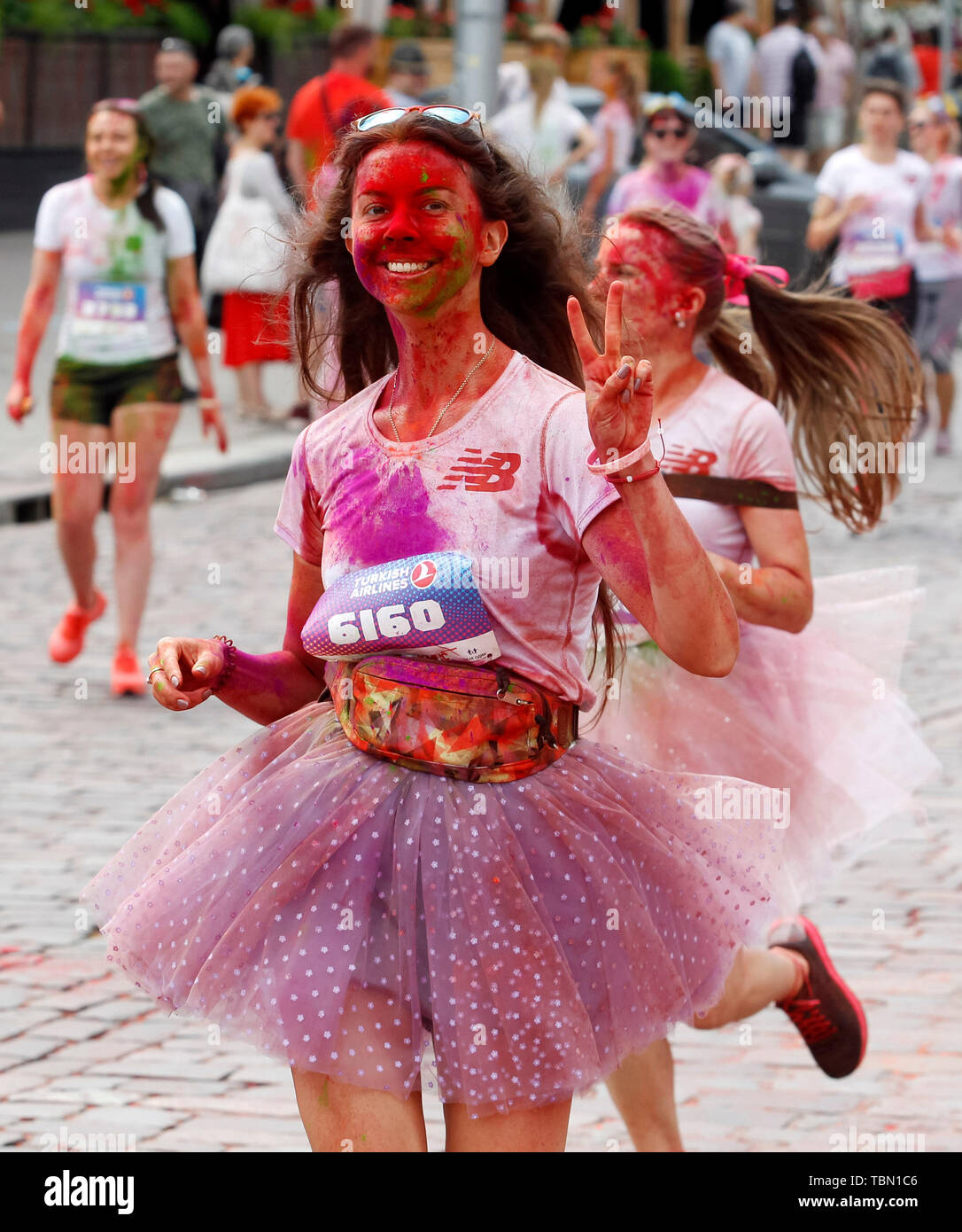 Woman showered in colours shows the peace sign during the run. The Color Run, also known as 'the happiest 5,000 meters on the planet', is an event series and paint race, its first event was in the United States in January 2012 since then the run has spread across the globe leaving a trail of color and happy runners across different continents and countries. The untimed event has no winners or prizes, but runners are showered with colored powder, made of food-grade corn starch, at stations along the run. In Ukrainian capital the first time Kyiv Color Run started in 2014. - Stock Image
