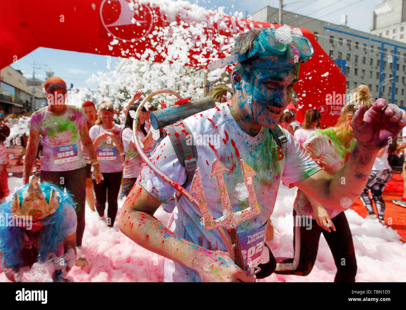 A participant runs while showered with colours during the event. The Color Run, also known as 'the happiest 5,000 meters on the planet', is an event series and paint race, its first event was in the United States in January 2012 since then the run has spread across the globe leaving a trail of color and happy runners across different continents and countries. The untimed event has no winners or prizes, but runners are showered with colored powder, made of food-grade corn starch, at stations along the run. In Ukrainian capital the first time Kyiv Color Run started in 2014. - Stock Image