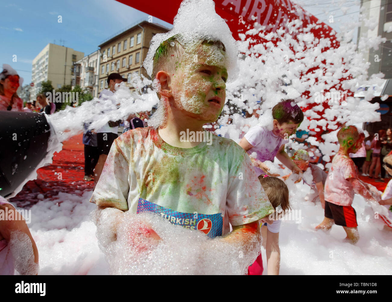 A kid showered with colours during the event. The Color Run, also known as 'the happiest 5,000 meters on the planet', is an event series and paint race, its first event was in the United States in January 2012 since then the run has spread across the globe leaving a trail of color and happy runners across different continents and countries. The untimed event has no winners or prizes, but runners are showered with colored powder, made of food-grade corn starch, at stations along the run. In Ukrainian capital the first time Kyiv Color Run started in 2014. - Stock Image