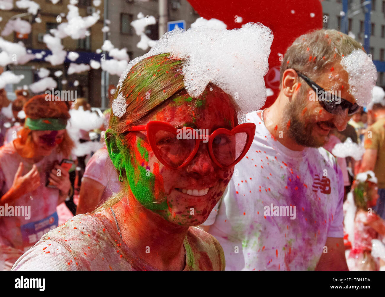 Woman with heart glasses showered in colours during the event. The Color Run, also known as 'the happiest 5,000 meters on the planet', is an event series and paint race, its first event was in the United States in January 2012 since then the run has spread across the globe leaving a trail of color and happy runners across different continents and countries. The untimed event has no winners or prizes, but runners are showered with colored powder, made of food-grade corn starch, at stations along the run. In Ukrainian capital the first time Kyiv Color Run started in 2014. - Stock Image