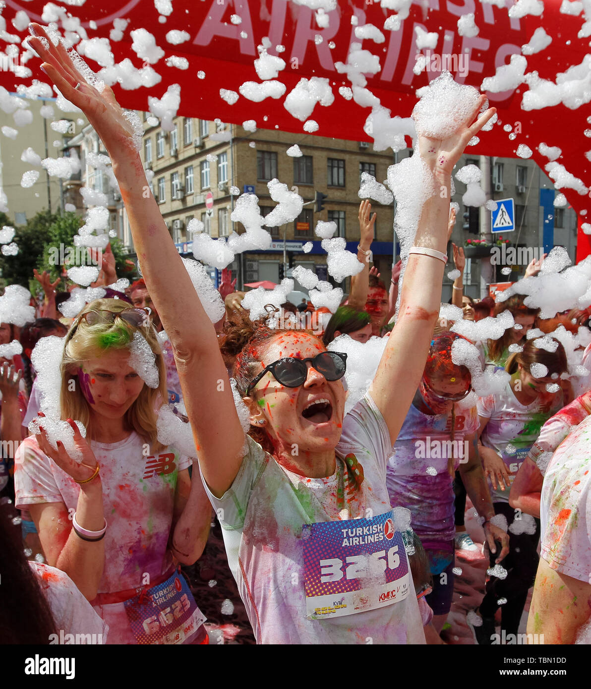 Woman screams with excitement during the event. The Color Run, also known as 'the happiest 5,000 meters on the planet', is an event series and paint race, its first event was in the United States in January 2012 since then the run has spread across the globe leaving a trail of color and happy runners across different continents and countries. The untimed event has no winners or prizes, but runners are showered with colored powder, made of food-grade corn starch, at stations along the run. In Ukrainian capital the first time Kyiv Color Run started in 2014. - Stock Image