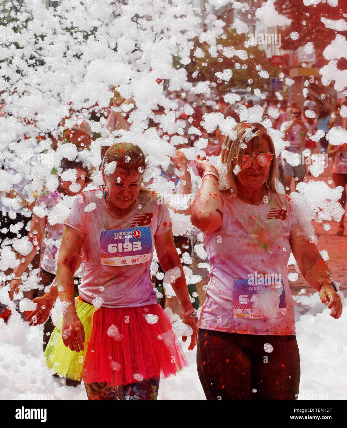 Participants being showered with colours during the event. The Color Run, also known as 'the happiest 5,000 meters on the planet', is an event series and paint race, its first event was in the United States in January 2012 since then the run has spread across the globe leaving a trail of color and happy runners across different continents and countries. The untimed event has no winners or prizes, but runners are showered with colored powder, made of food-grade corn starch, at stations along the run. In Ukrainian capital the first time Kyiv Color Run started in 2014. - Stock Image