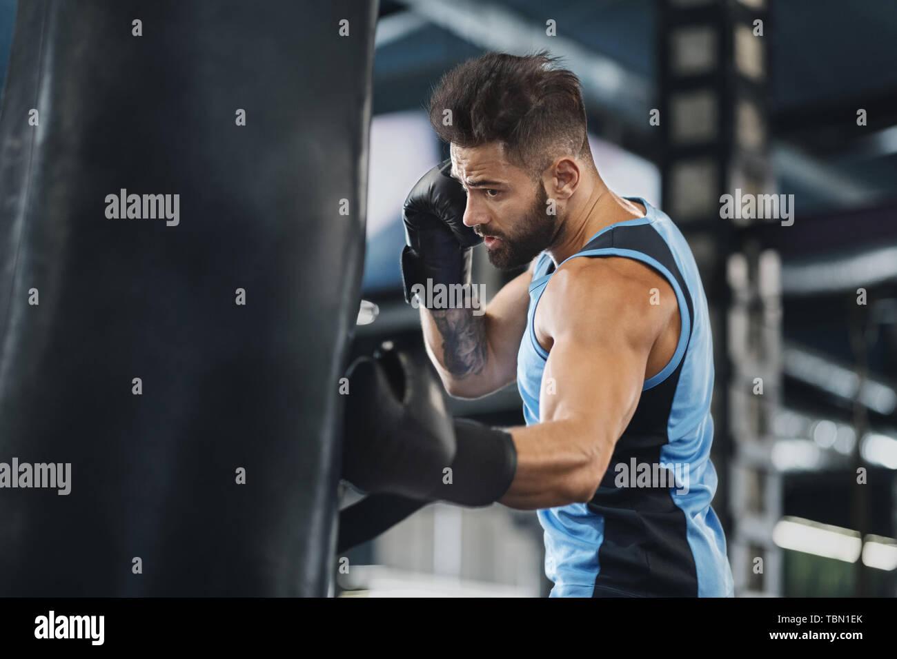 Active guy punching boxing bag at gym Stock Photo