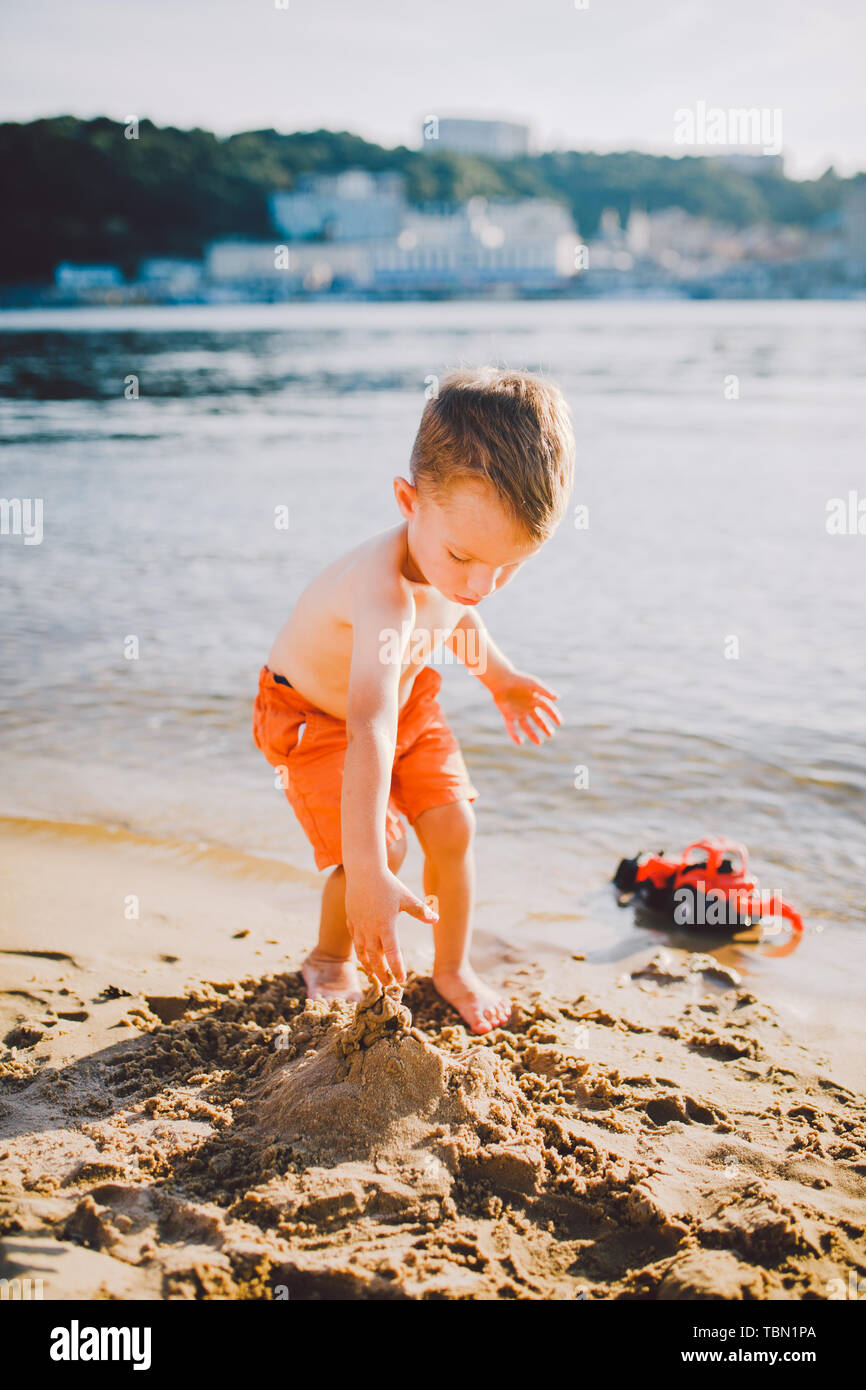 Subject construction and heavy industry. Abstraction child boy playing on the sand near the river in the summer toy red tractor model, excavator - Stock Image