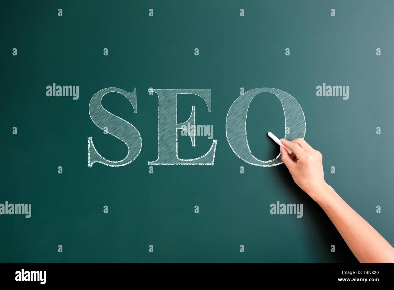 seo written on blackboard - Stock Image