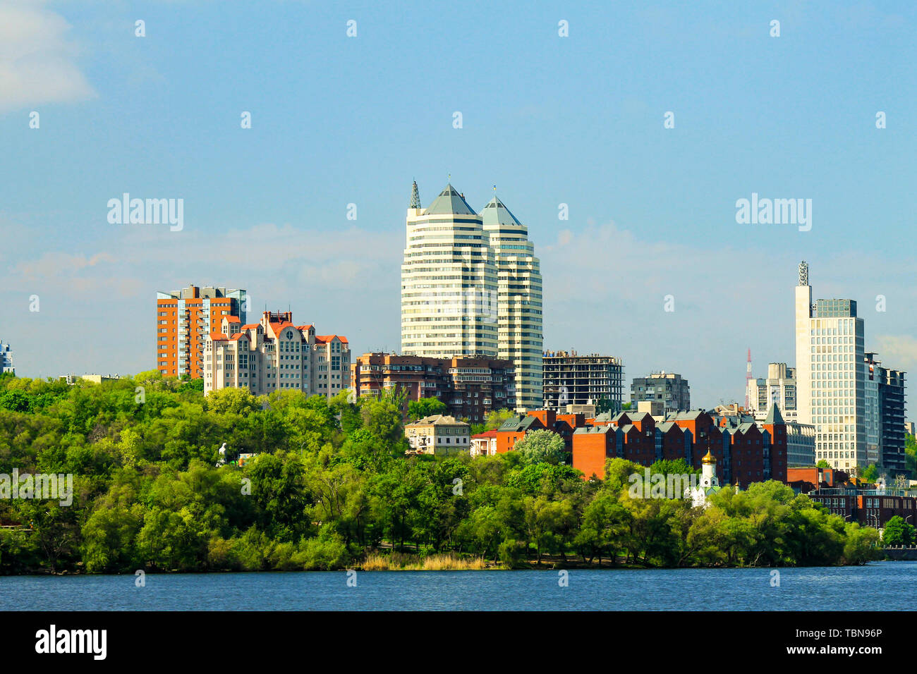Beautiful towers, buildings and skyscrapers in the River in the early summer morning. Dnepropetrovsk, city Dnipro Ukraine, spring cityscape - Stock Image