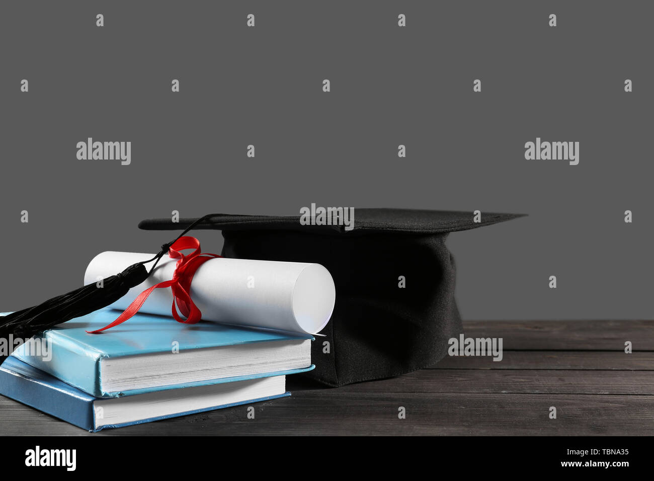 Mortar board, diploma and books on table. Concept of high school graduation - Stock Image