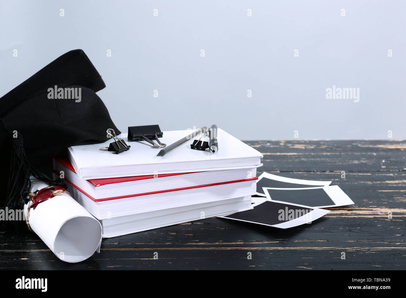 Mortar board, diploma, books and stationery on table. Concept of high school graduation - Stock Image