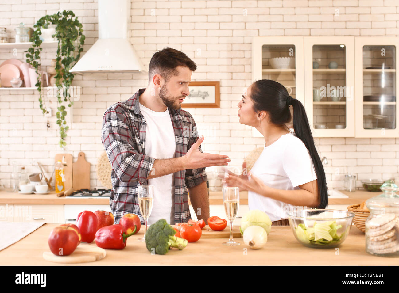 Young couple quarreling in kitchen - Stock Image