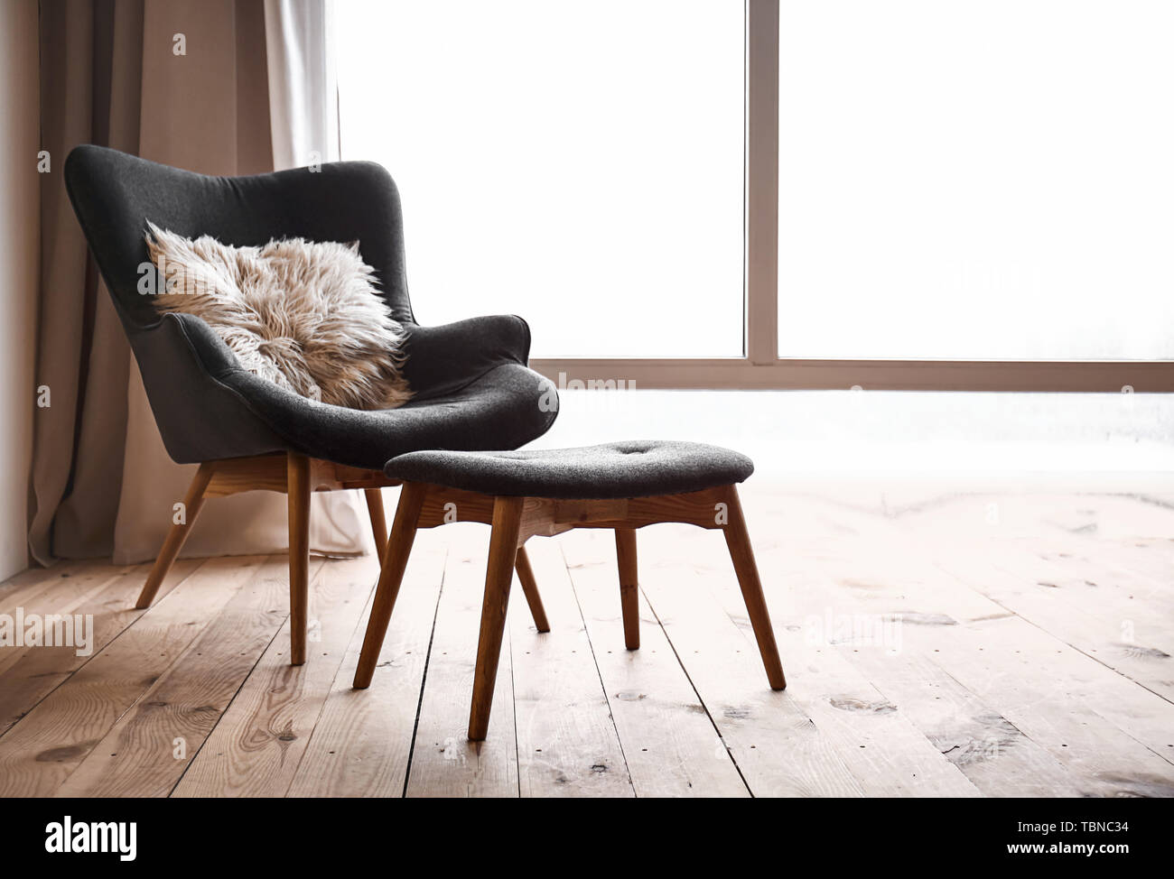 Comfortable armchair and footstool near window in flat - Stock Image