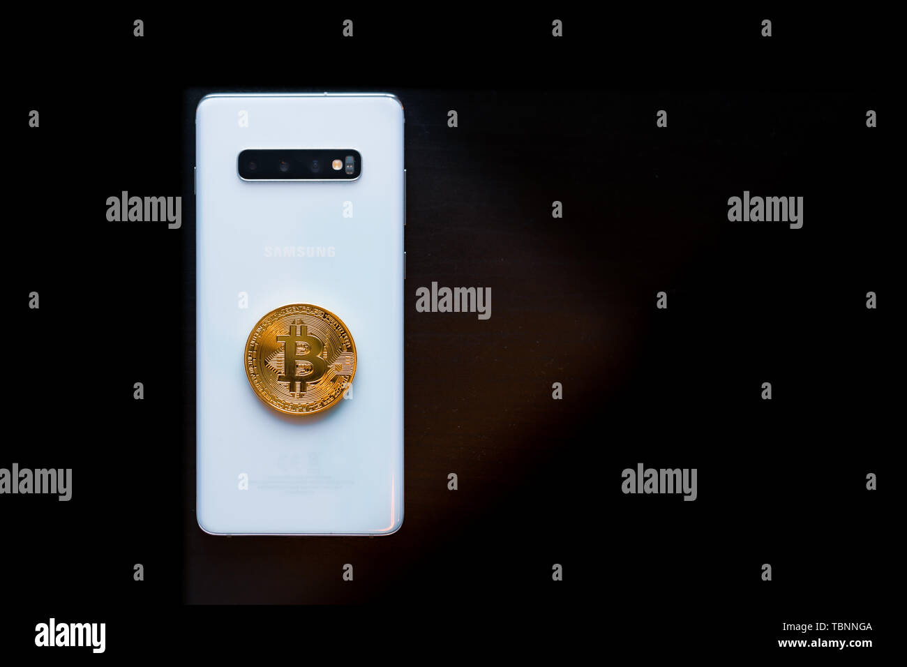 Smart Phone with a Physical Bitcoin on top - Stock Image