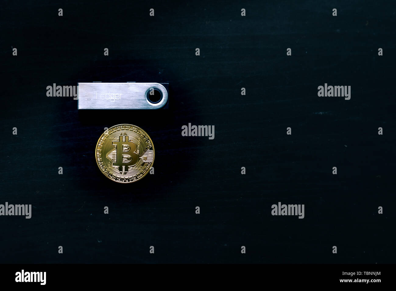 Physical bitcoin sitting underneath a Ledger Nano S secure cold wallet - Stock Image