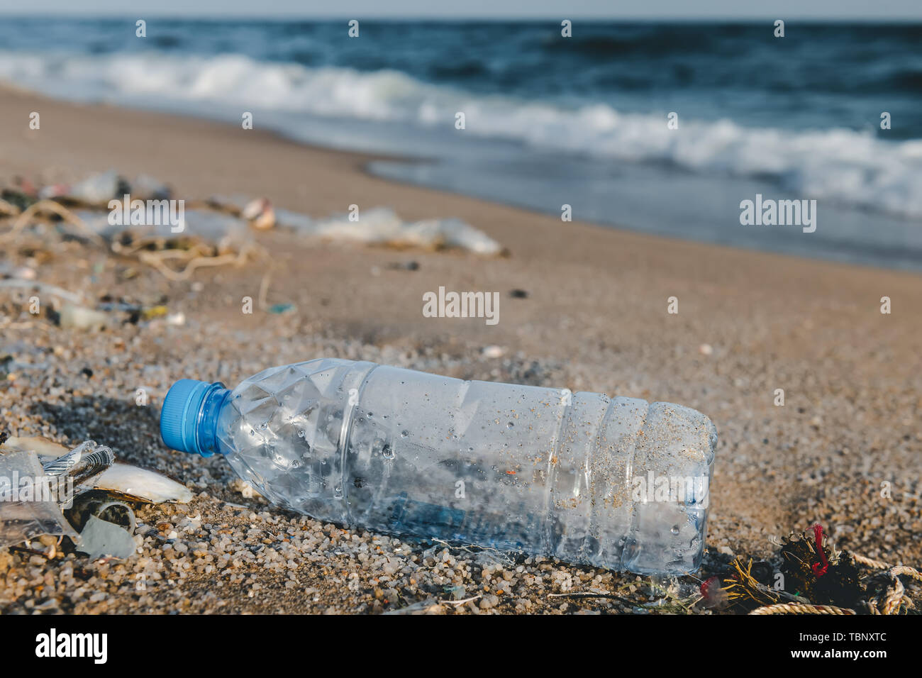 Plastic bottle garbage on the beach in pollution sea scape  environment with sun lighting. - Stock Image
