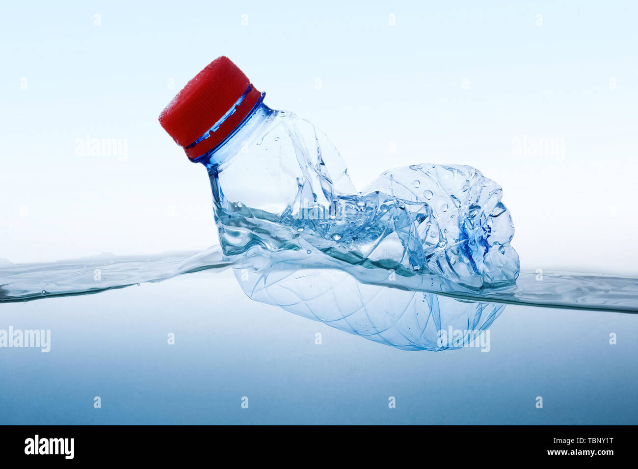 Plastic water bottles pollution in water. Environment concept. Blue background - Stock Image