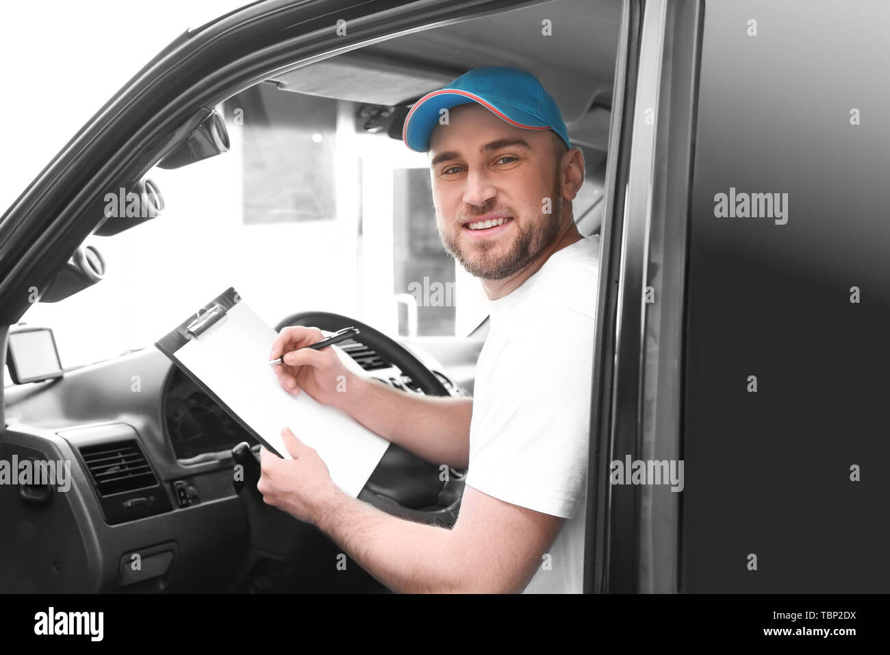 Handsome delivery man sitting in car - Stock Image