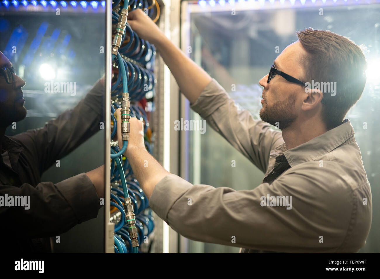 Serious skilled young data center engineer in glasses standing at mainframe and examining cables while doing checkup - Stock Image