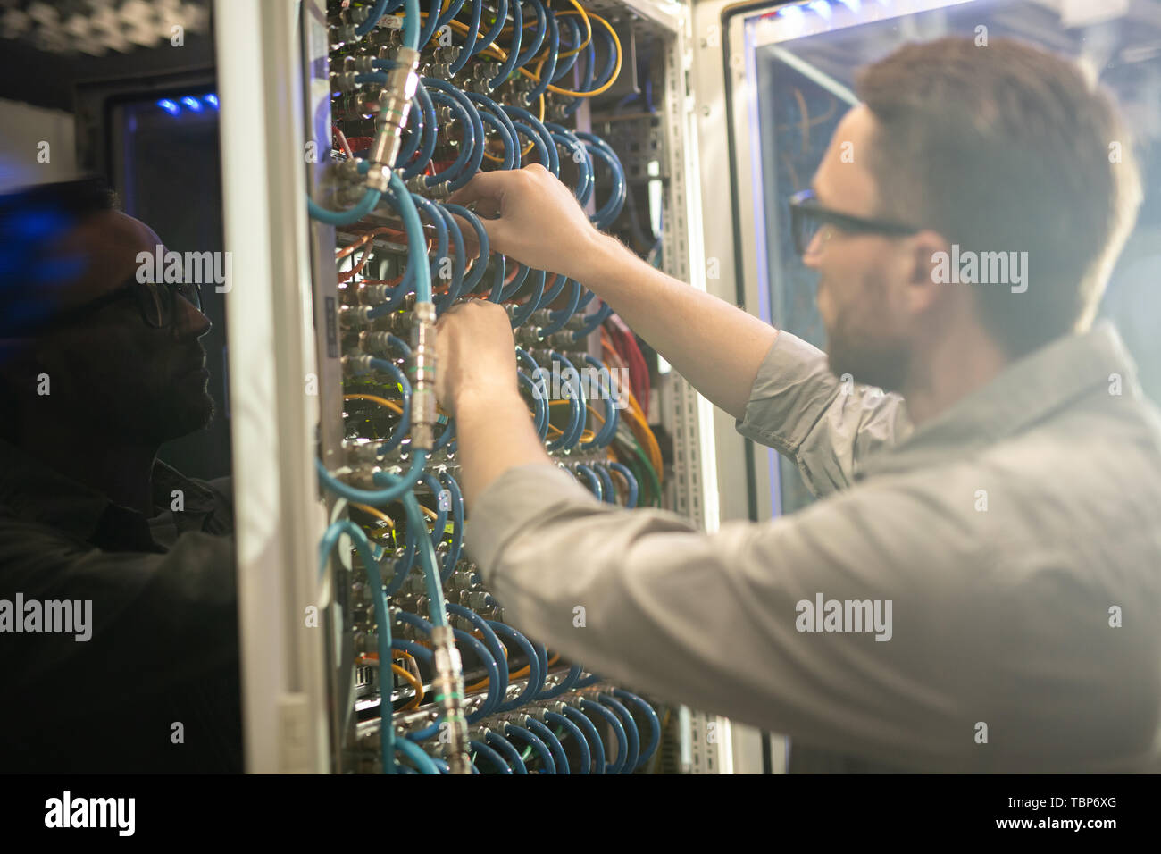 Busy young network engineer standing at open cabinet of mainframe and adjusting cables while fixing server - Stock Image