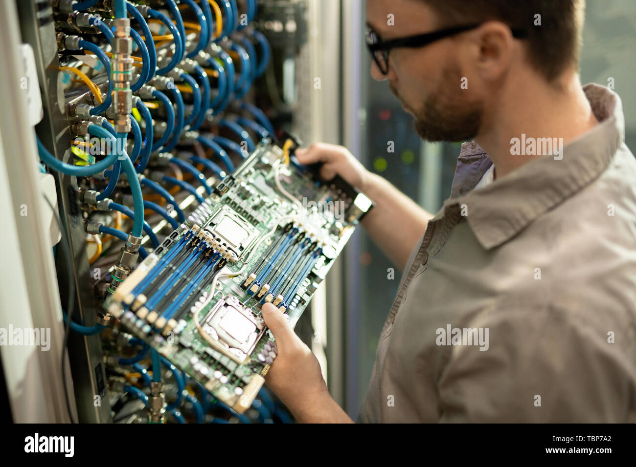 Close-up of serious bearded IT support specialist standing by cabinet of mainframe and examining motherboard of server - Stock Image