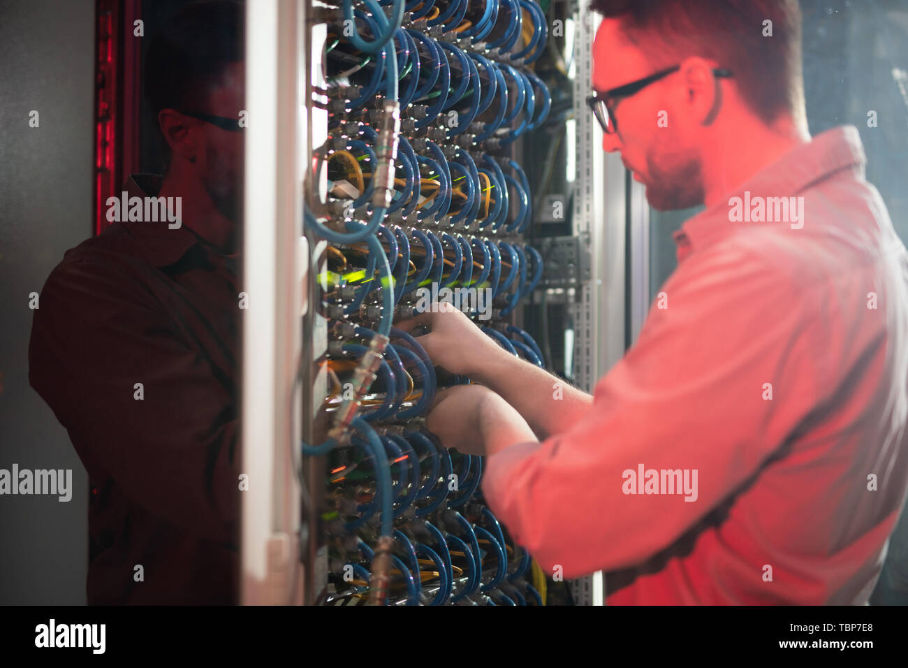 Serious busy young IT specialist in glasses standing by powerful mainframe and examining cables while maintaining networking system - Stock Image