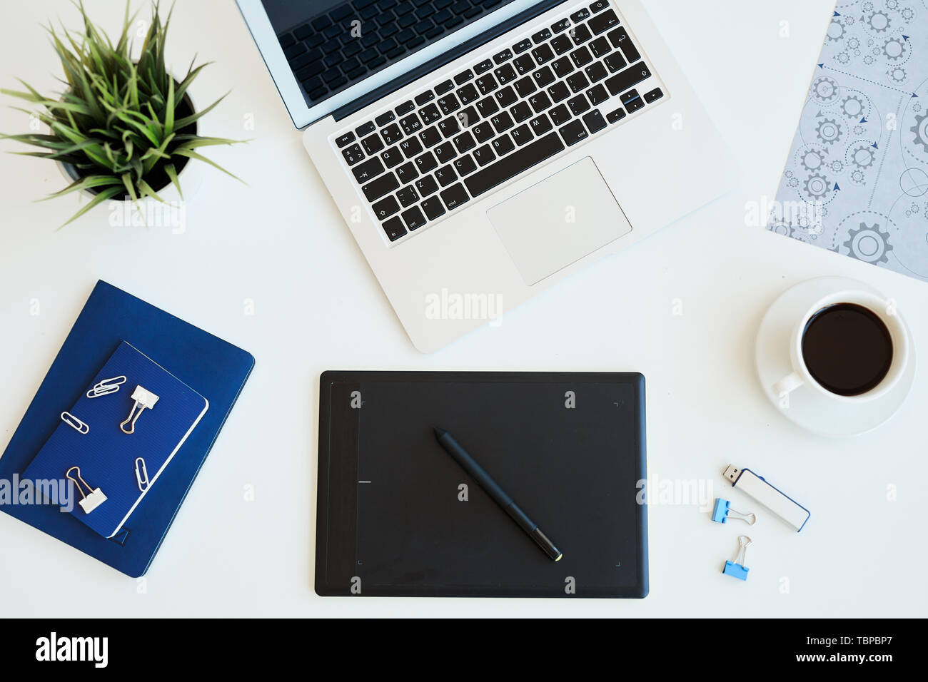 High angle view of digital graphic drawing tablet, open laptop, diaries and cup of coffee on desk - Stock Image