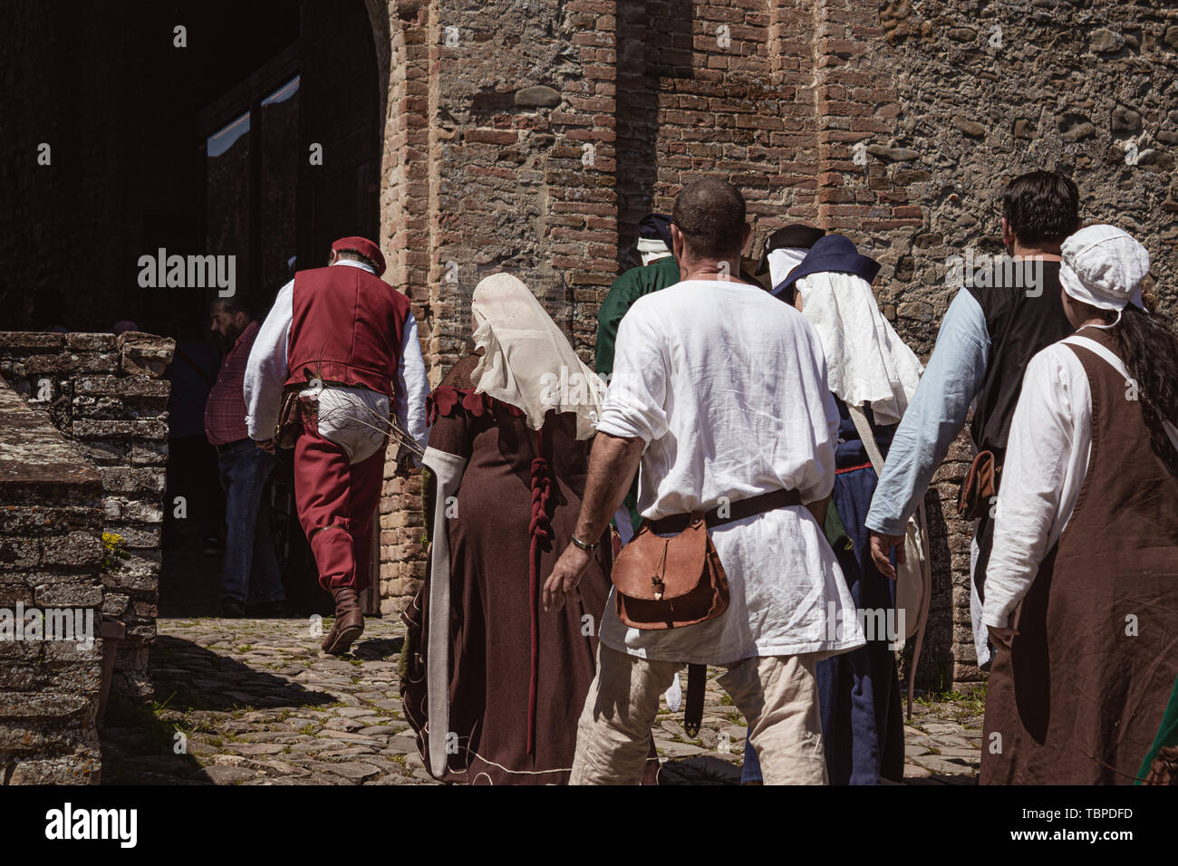 Group of unrecognizable people dressed in medieval costumes walking down an ancient street leading to a castle - Stock Image