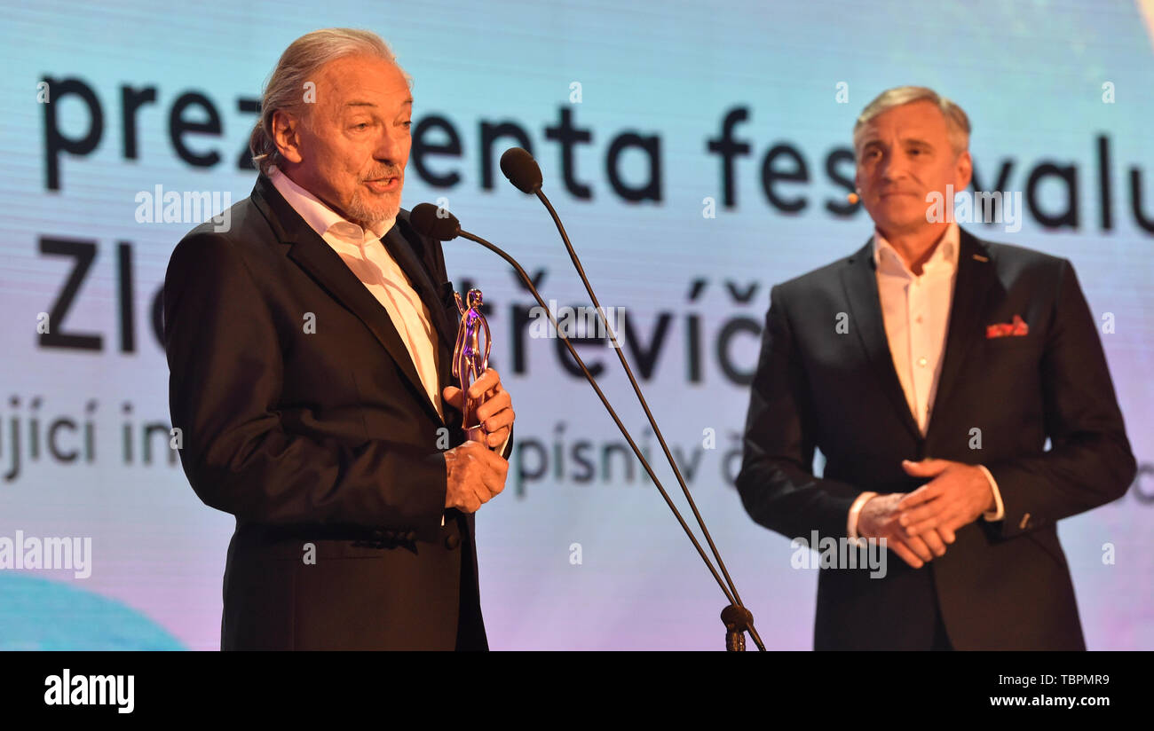 """Zlin, Czech Republic. 31st May, 2019. Czech singer Karel Gott, left, takes the """"Golden Slipper"""" award for exceptional interpretation of songs in Czech films, within the 59th Zlin Film Festival - International film festival for children and youth, in Zlin, Czech republic, on May 31, 2019. On the right side is seen moderator Jan Censky. Credit: Dalibor Gluck/CTK Photo/Alamy Live News Stock Photo"""