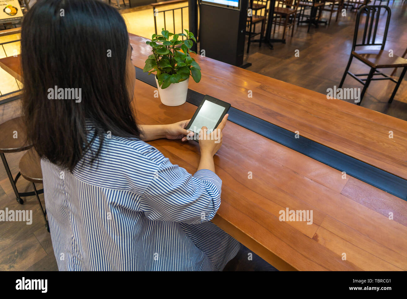 Woman focus on reading ebook with tablet on hands - Stock Image