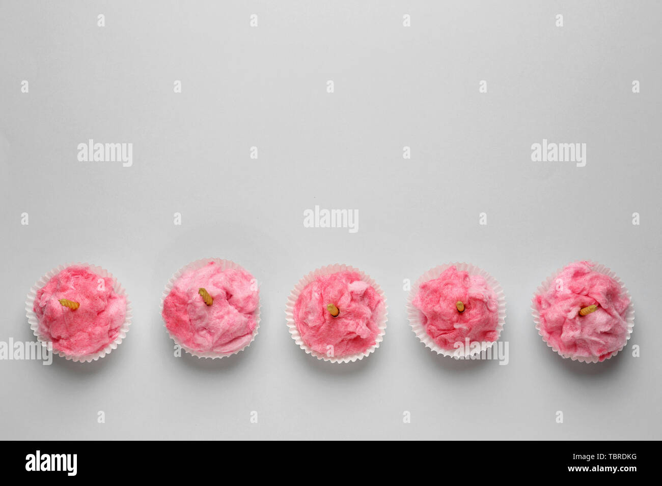 Tasty cotton candy with candles on grey background - Stock Image