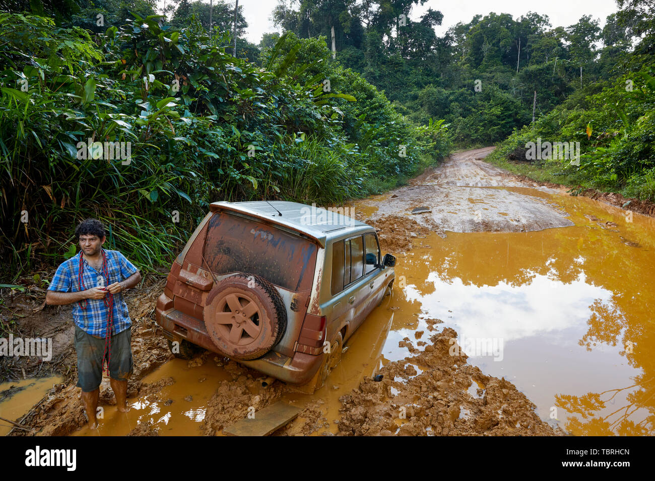 4X4 vehicle stuck in a deep muddy pothole on Linden-Lethem Road in Guyana South America Stock Photo