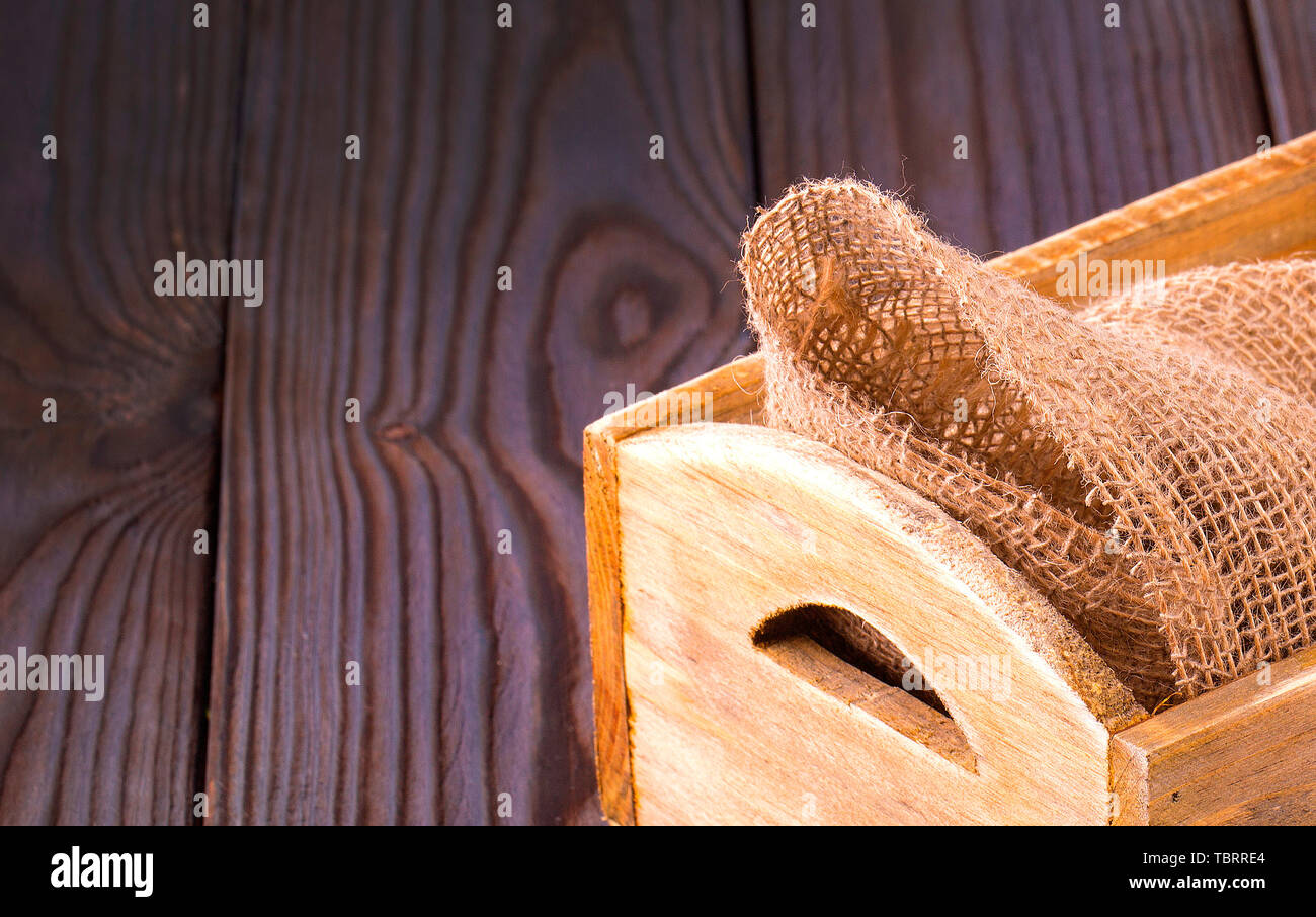 the Wooden box on sack cloth on wooden background - Stock Image
