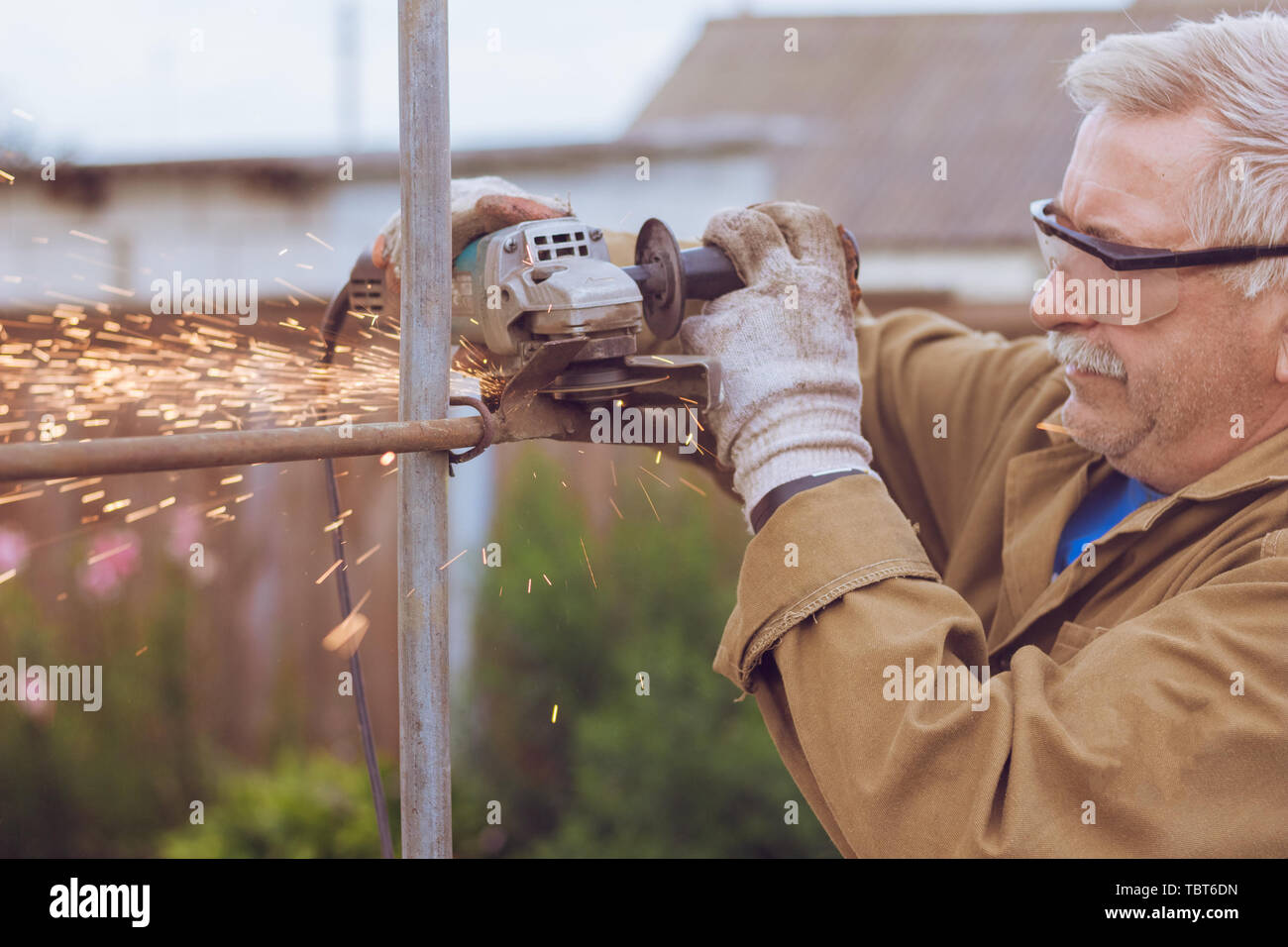 Hazardous work grinder, operating in the protection glasses metal cutting - Stock Image