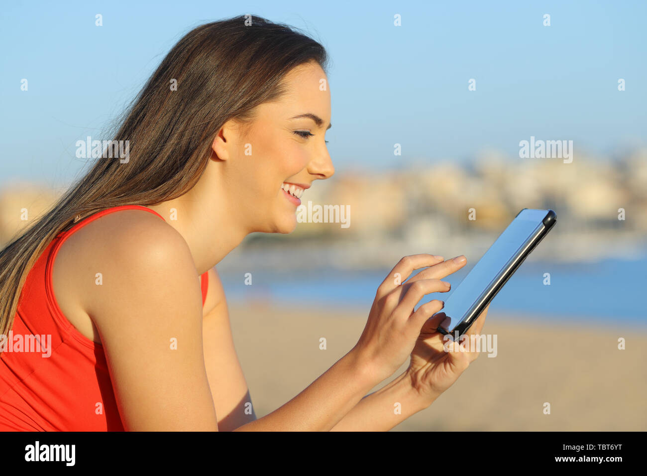 Profile of a happy woman browsing tablet online content on the beach - Stock Image