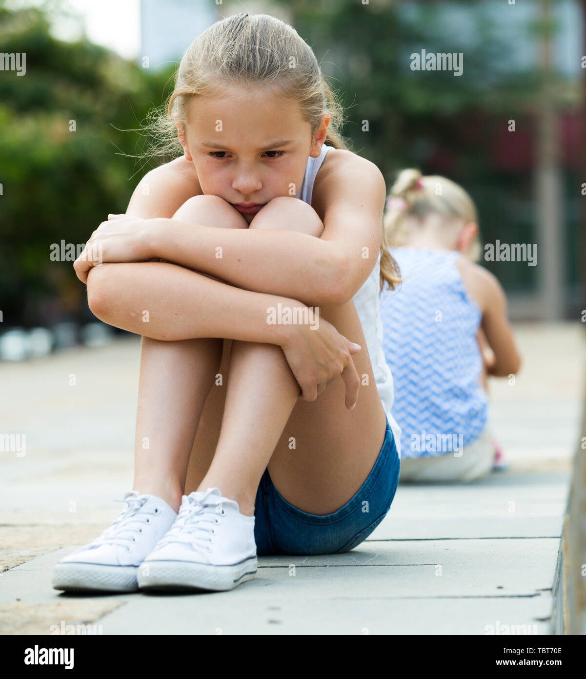 Two offended little girls not talking to each other after quarrel outdoors - Stock Image