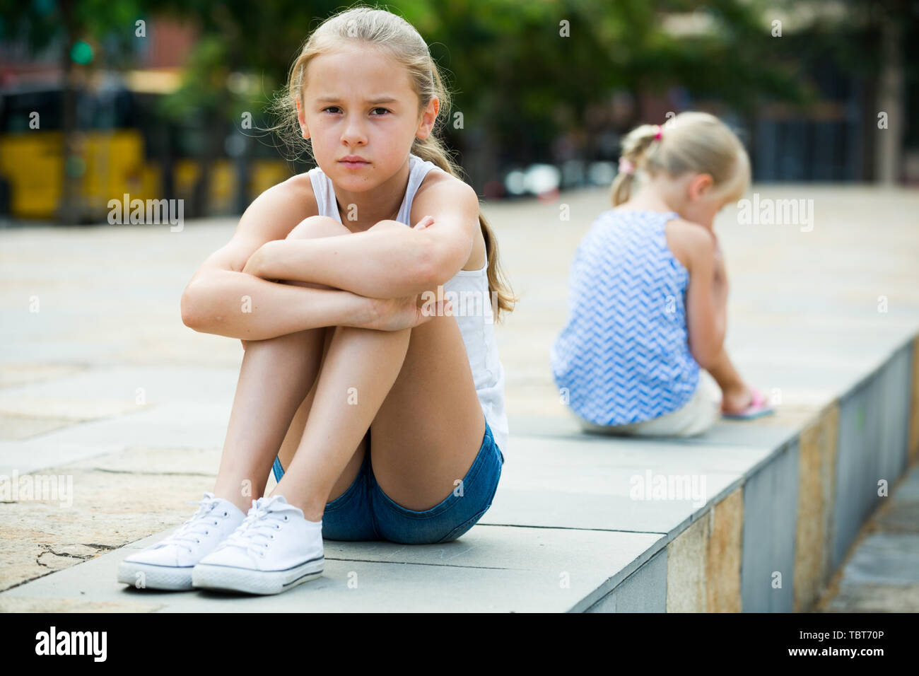 Small sisters offended and upset after quarrel outside - Stock Image