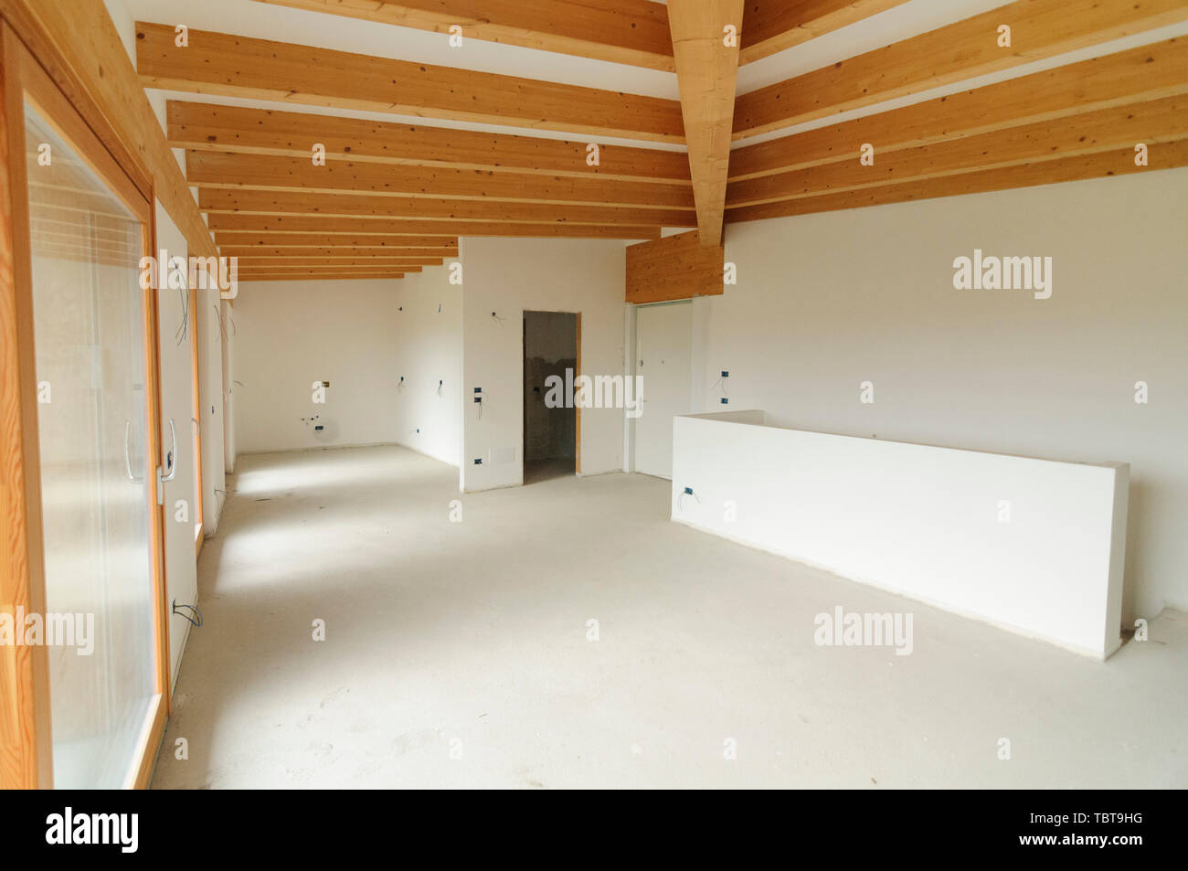 Building site or home renovation in progress: empty open space with large windows and exposed wooden beams Stock Photo