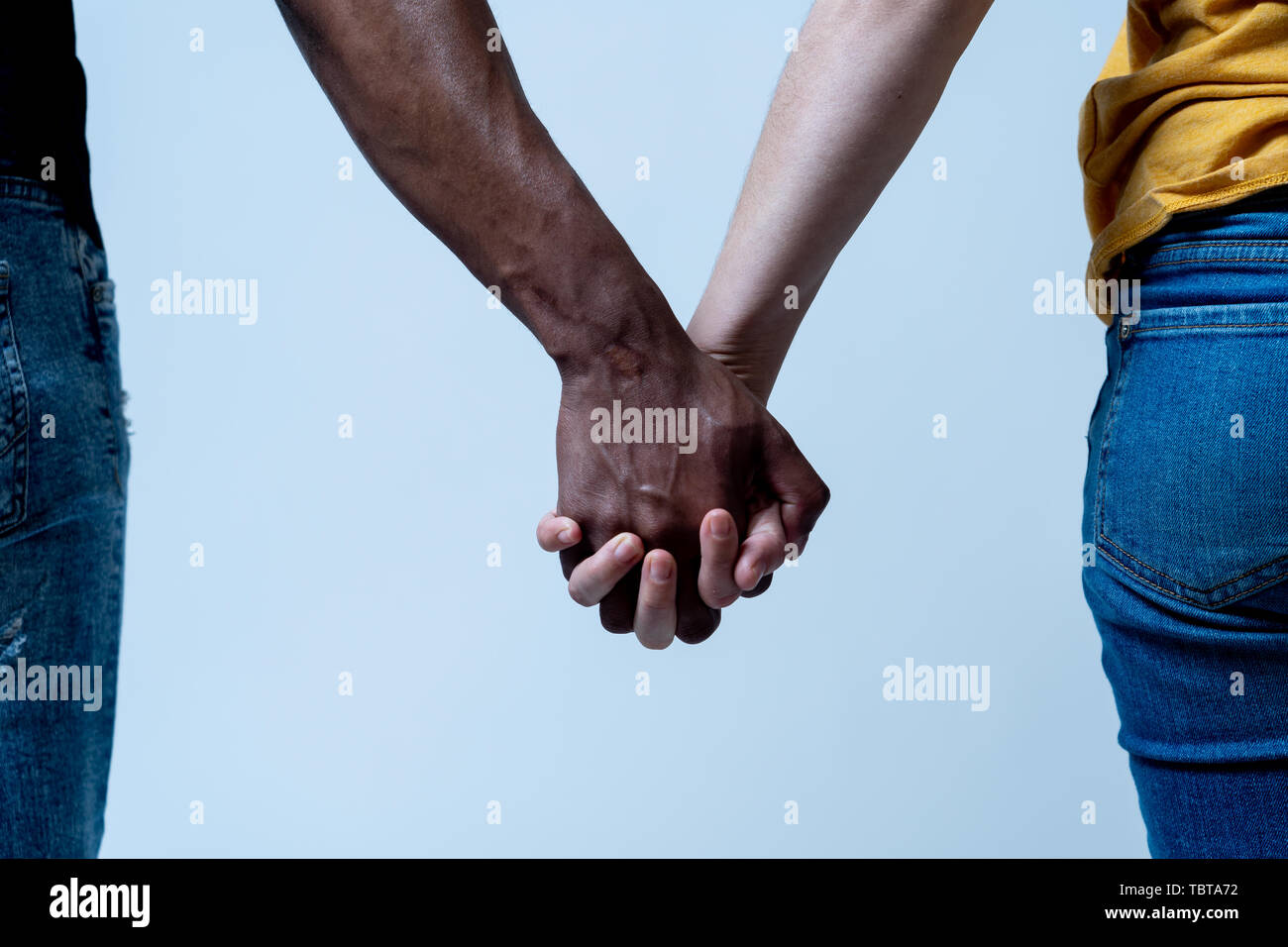Multiracial couple holding hands together in love. White and black skin arms holding together. Conceptual image of world unity interracial love and un - Stock Image