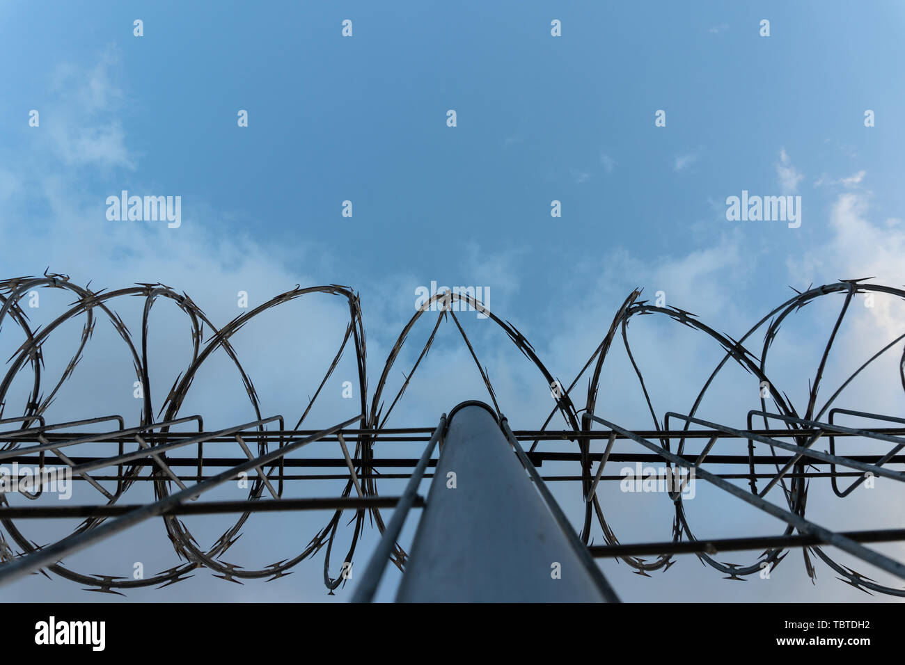Barbed wire fence with bright blue sky to feel silent and lonely and want freedom. Dramatic clouds behind barbed wire fence on a prison wall. - Stock Image